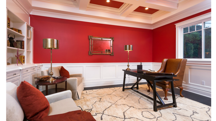 The home office takes a departure from the more public rooms in the home with a bright shade of red paint on the walls and ceiling. The custom coffered ceiling is elegant and matches the white wainscoting on the lower walls and built-in shelving.