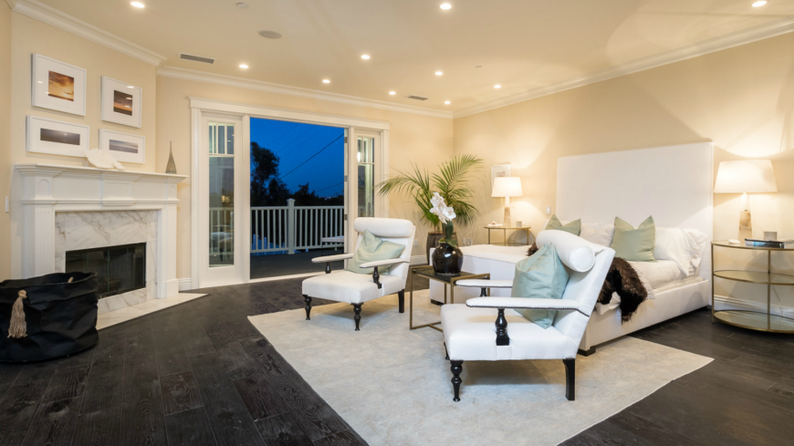 The spacious primary bedroom on the second level has a beautiful enclosed fireplace in marble and wood, topped by four sunset pictures. The white bed frame has an enormously tall headboard and is flanked by two white chairs. Glass doors lead to the balcony overlooking the backyard.