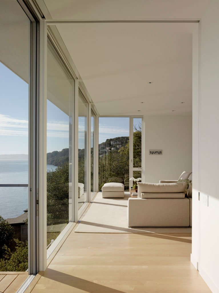 Another short hallway leads to the primary bedroom, which has a balcony. Even from this angle, the home has a beautiful view of the water and of the surrounding hillside.