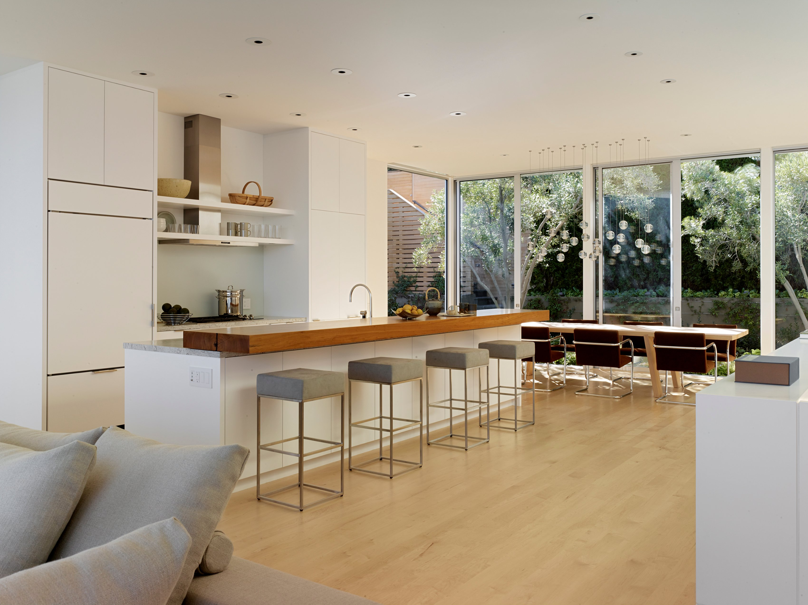 From the other side of the room, the lush private garden is visible through the floor-to-ceiling windows. The steep hill allows the second floor to have both easy backyard access and gorgeous views. The bar stools at the kitchen island are simple in design, with a cushy square pad to sit on.