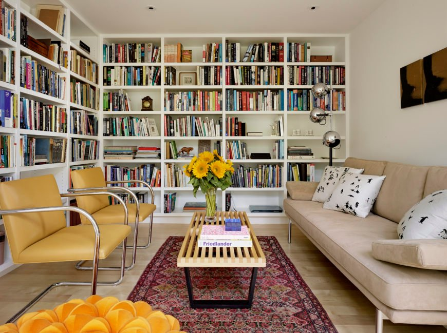 The L-shaped bookcases take up two of the three walls of the room and provide storage for hundreds of books. A modern floor lamp can be re-arranged for as much or as little light is desired.