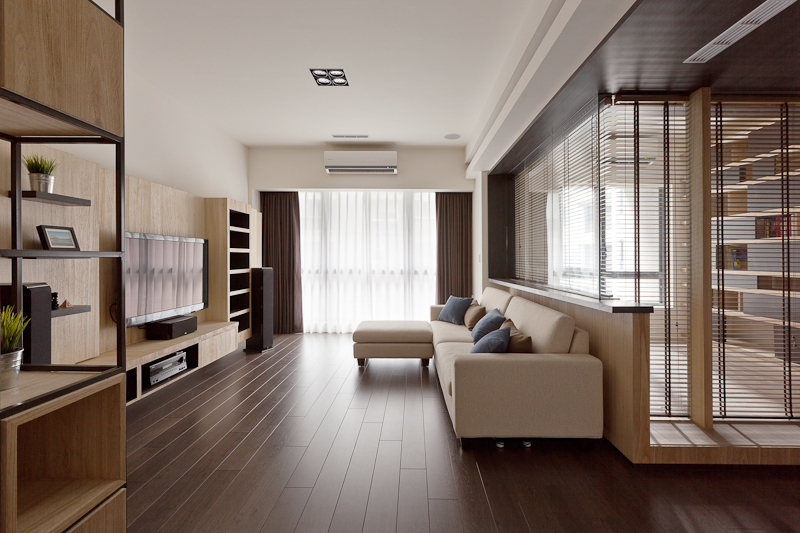 The living room is naturally lit through a large wall-size glass sliding door. Media components are mounted on a large wall-length cabinetry and shelving structure.