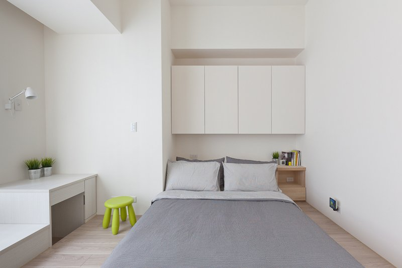 The bed stands below another set of sleek, minimalist cabinetry, with a small bedside table and built-in desk at left.