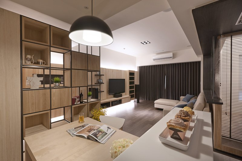 Angled shot from the kitchen showing the expanse of open flooring toward the living room and balcony doors.