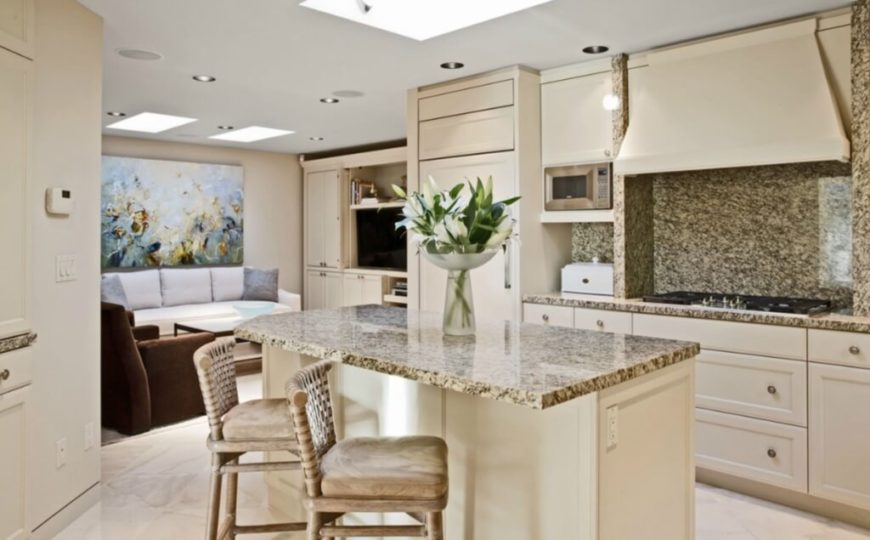 The kitchen features a mixture of beige and soft granite hues, with island countertop at center matching the large backsplash at right.