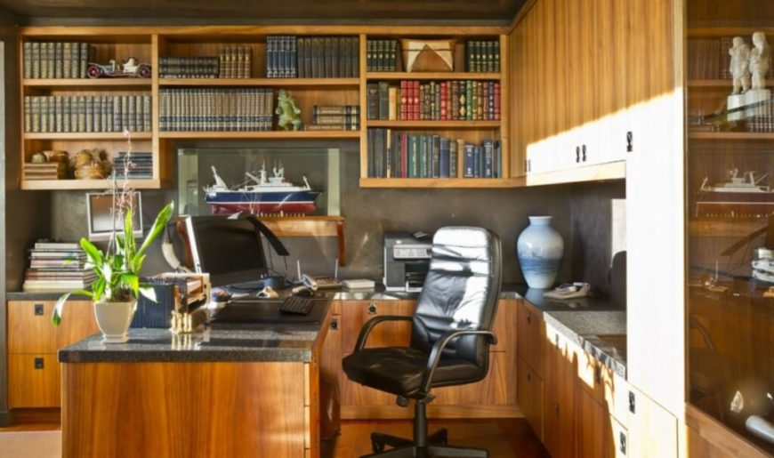 A home office in rich natural wood tones stands apart from the stark whiteness of much of the home. With full height shelving wrapped around a matching desk, this space evokes the wooded surroundings of the home.