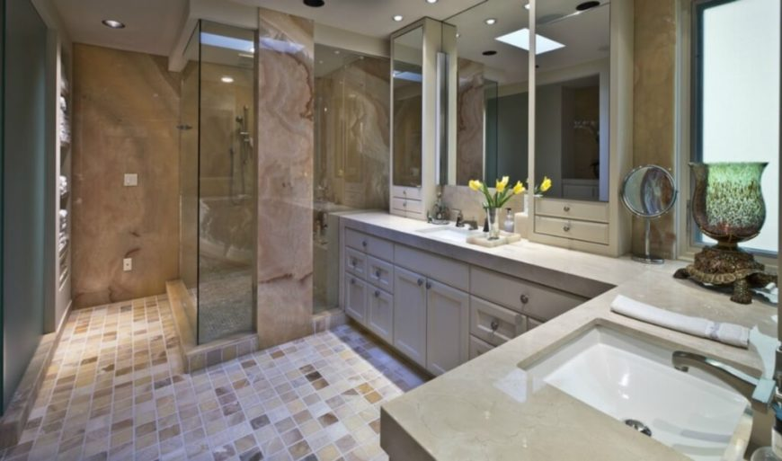 The large primary bath is filled with tonal variety, with multicolored tile flooring, beige countertops, and a glass enclosed shower supported by a massive marble column.
