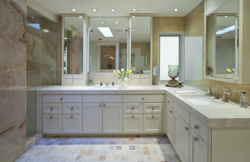 The large dual vanity wraps around two walls of the bathroom, featuring a larger mirror set to the left, with extra above-counter storage.