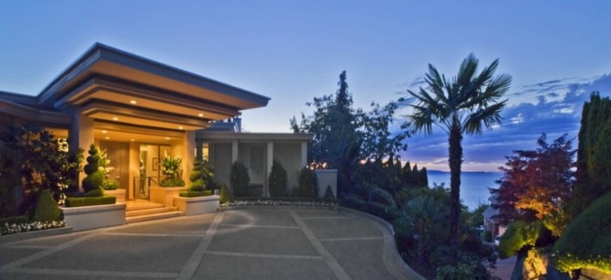 Approaching the home from the drive, a cornucopia of landscaping wraps the sharply defined modern structure. A large, illuminated overhang dominates the entrance.
