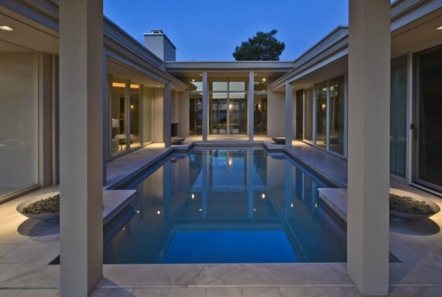 The entire home wraps around this central courtyard, featuring a lengthy pool. Columns support overhangs all around, while full height glass blends the interior and outdoor spaces.