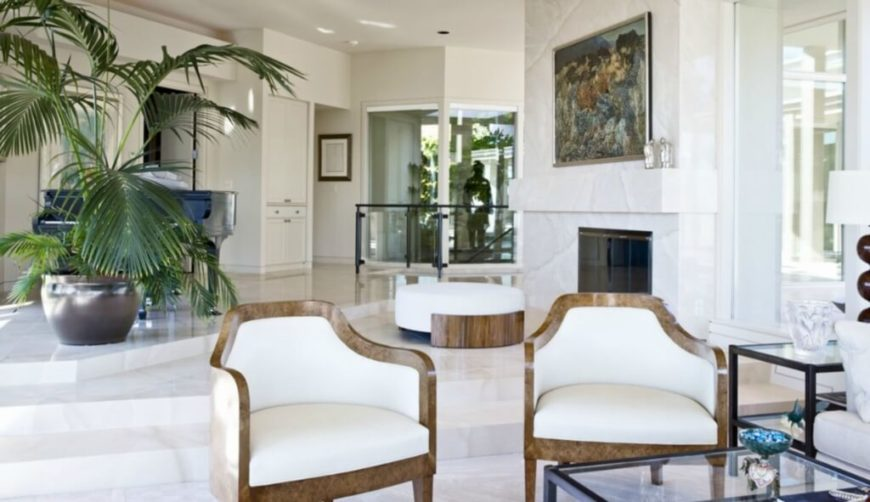 Looking back toward the entryway, we see a pair of polished wood frame accent chairs and a matching circular ottoman before the fireplace.