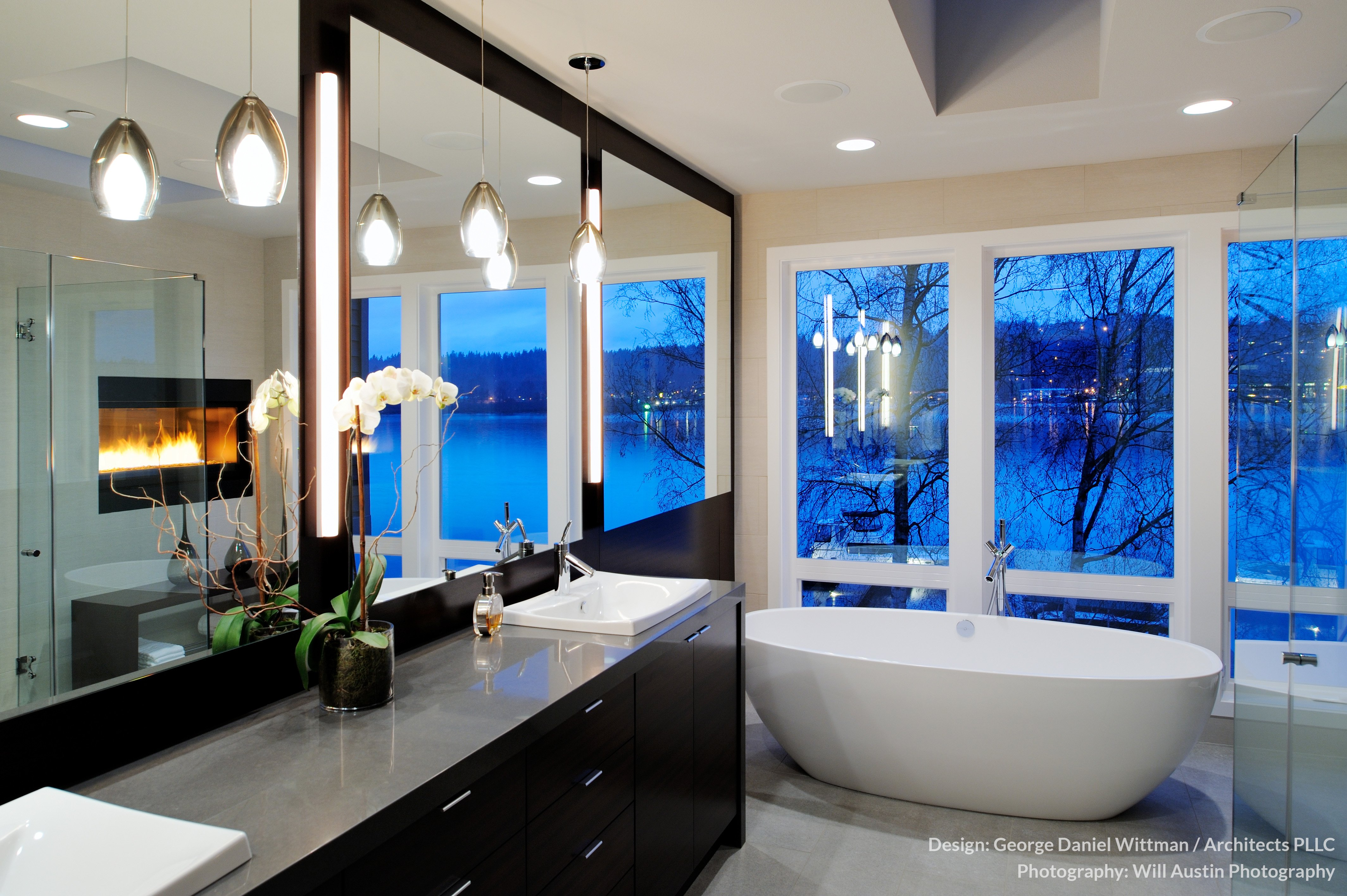 The primary bath houses a large pedestal tub with expansive views over the water via full height windows. All-glass shower enclosure can be seen at right.