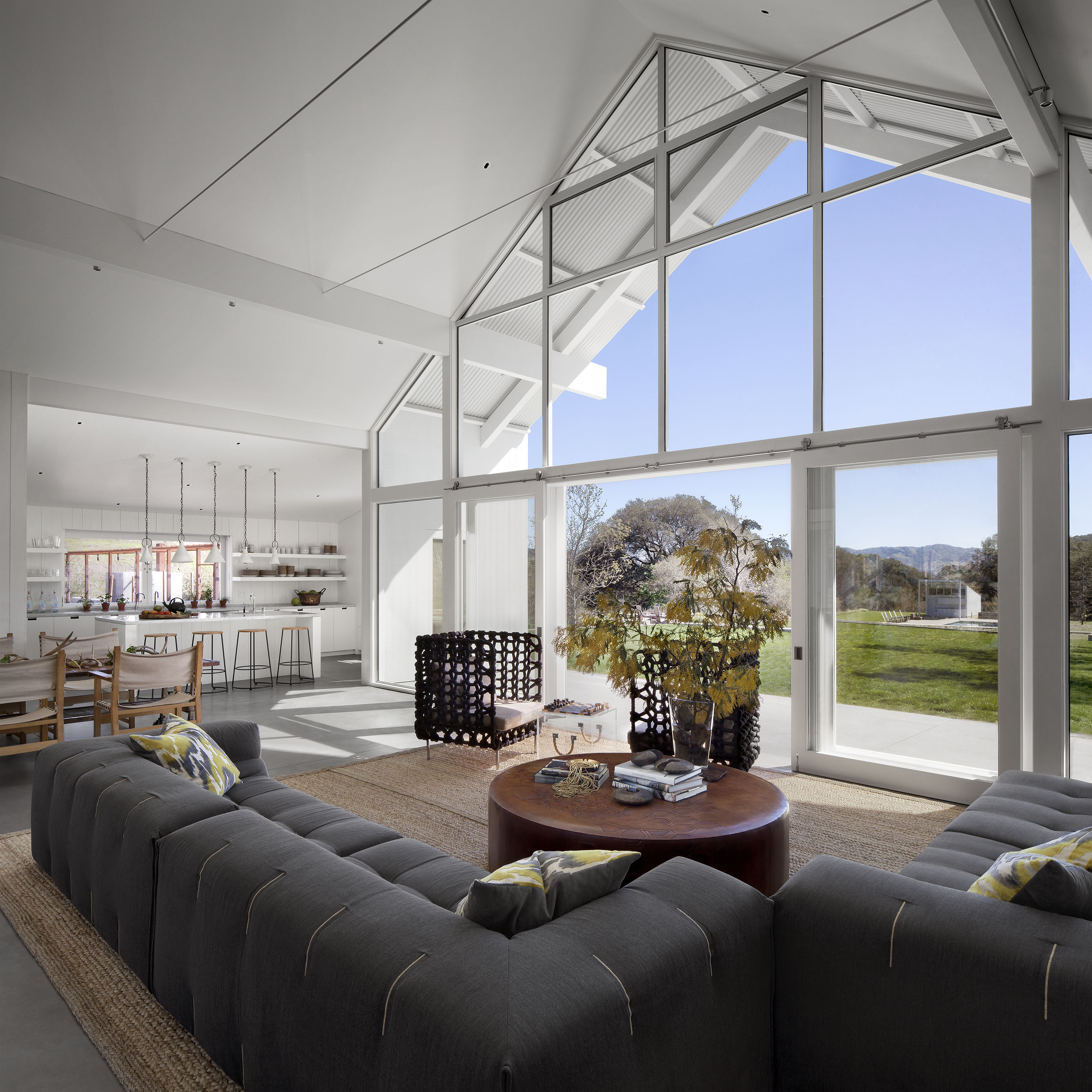 The central, open design body of the home situates a sprawling living room beneath full height glass panels, allowing for expansive views and a blending of indoor and outdoor visual spaces. Large sliding panels allow for fresh air and full access to the patio.