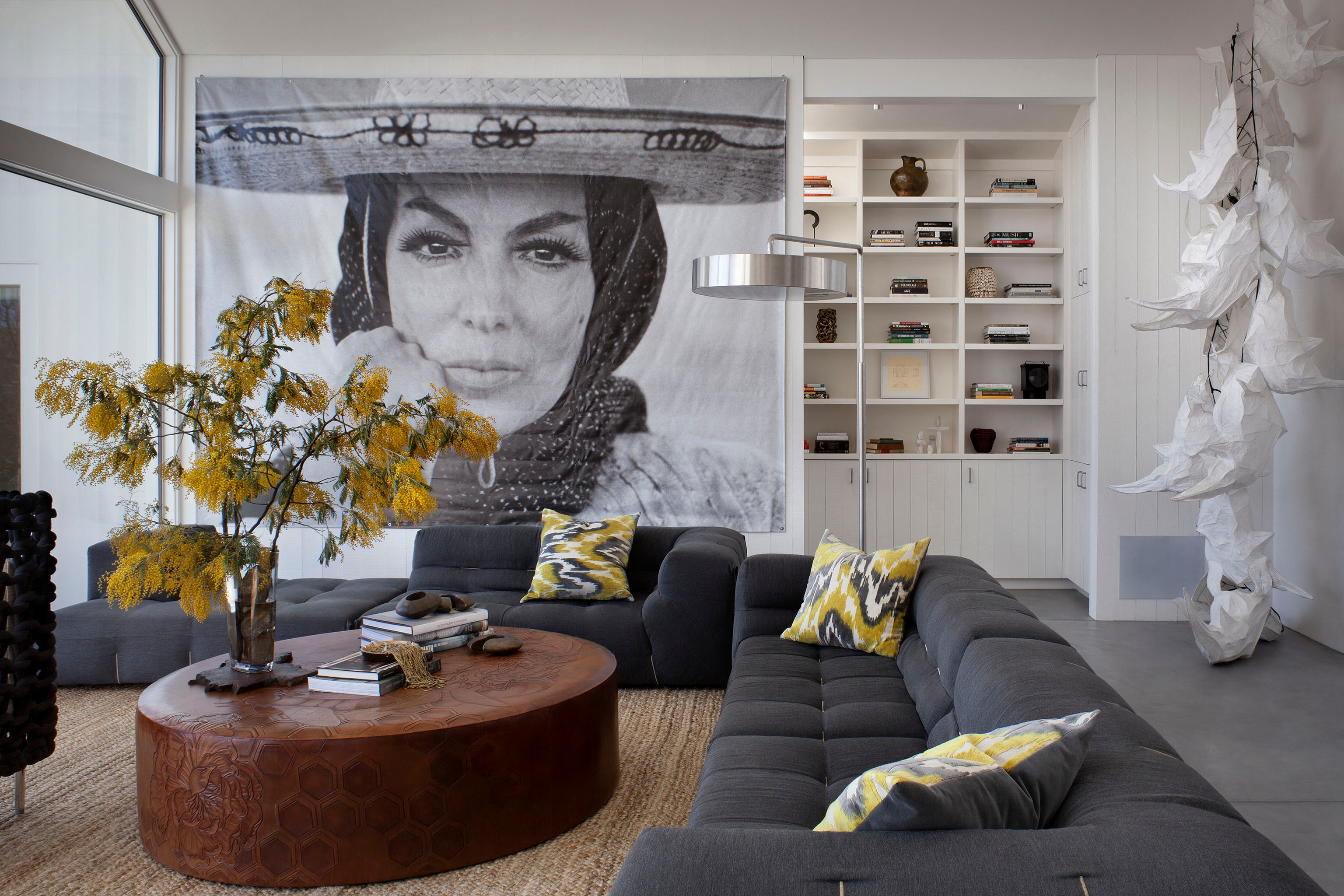 The neutral white and grey hues are countered by bursts of yellow, on the accent pillows and a large plant in the living room. Massive circular leather ottoman coffee table commands attention, while another striking art piece is seen on the far right.
