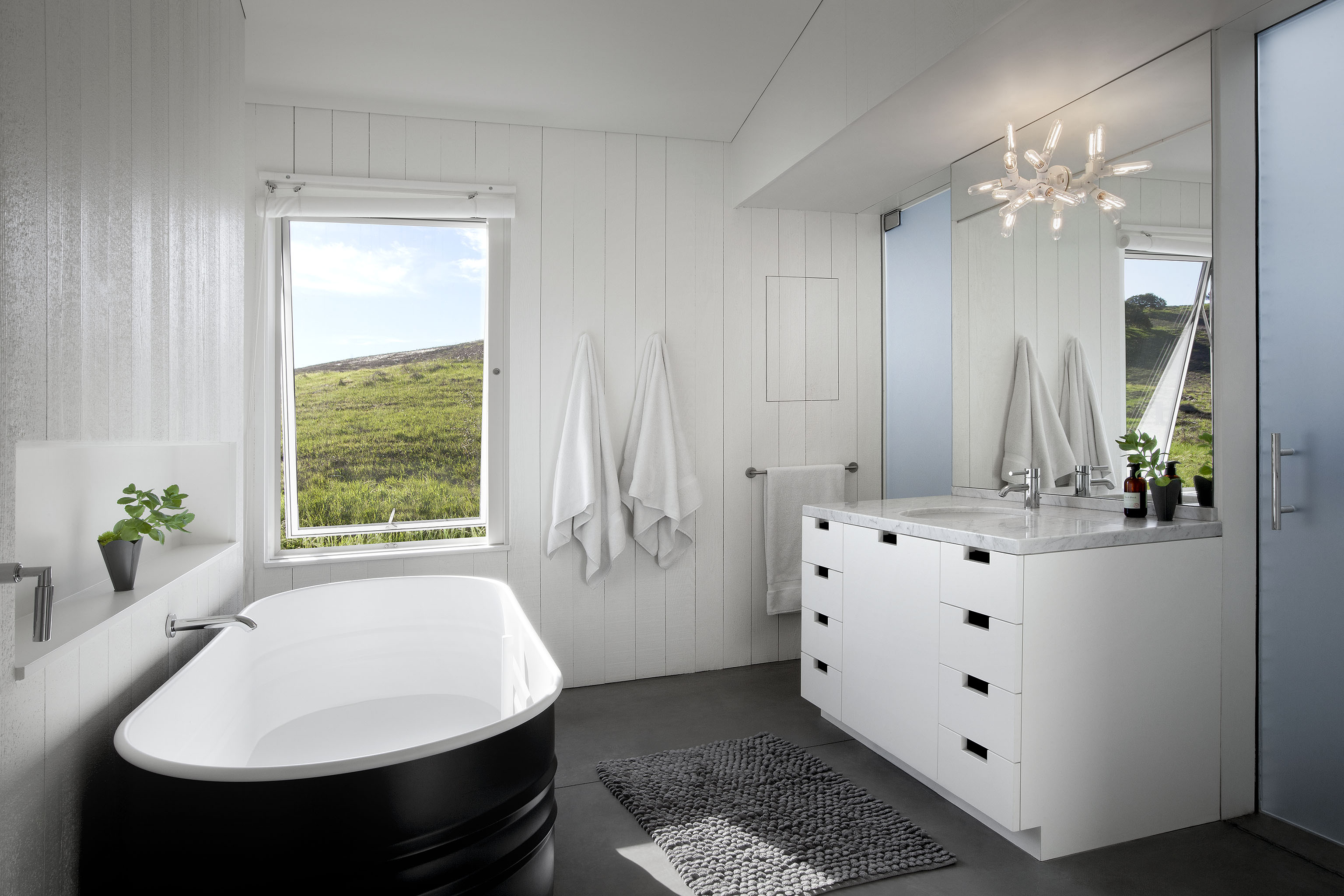 Bathroom reflects the muted tones of the living room, with bold white and soft grey mixing throughout. Large pedestal tub in black sits across from minimalist vanity with marble countertop.