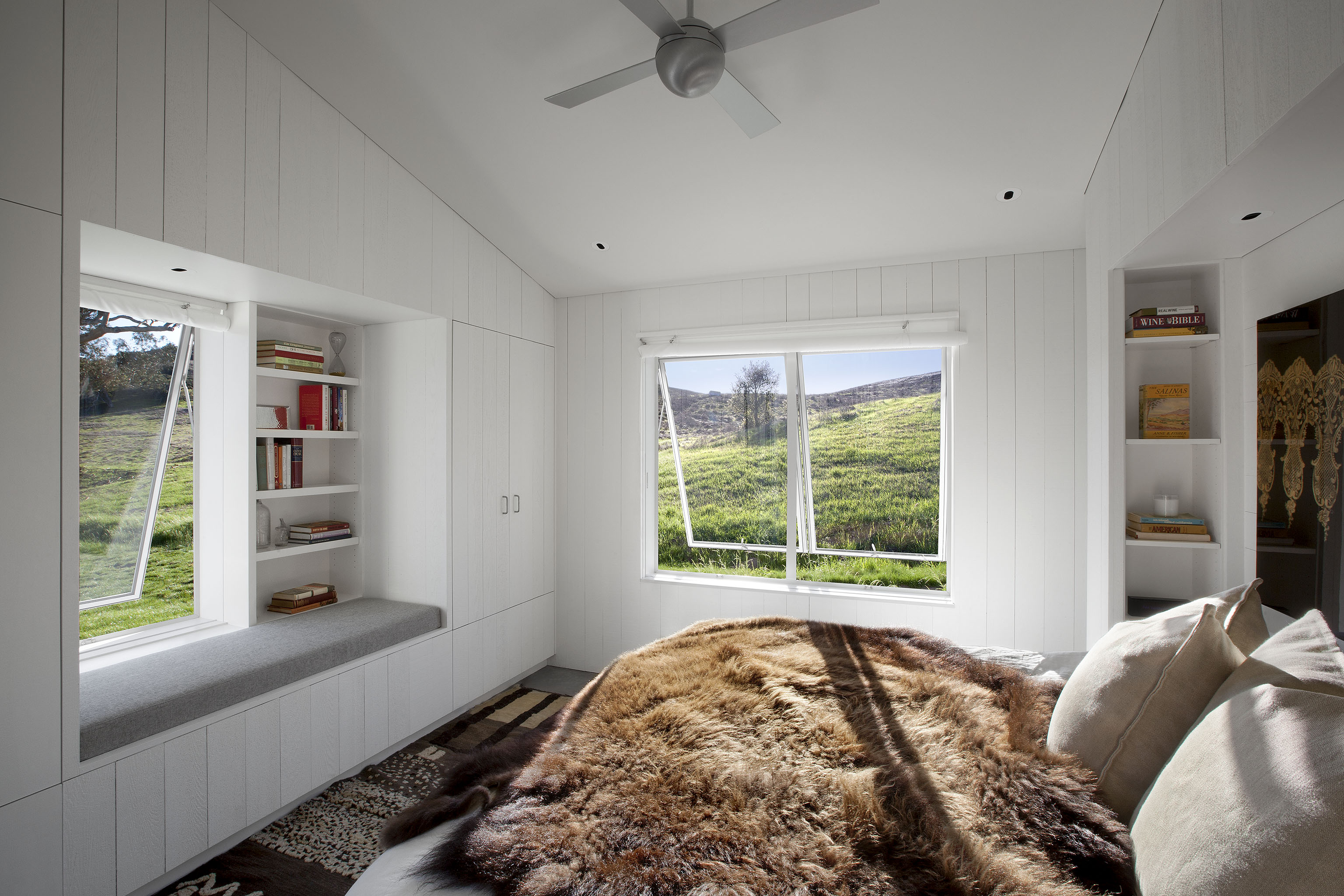Bedroom seen here is equipped with a large window seat and built-in shelving, plus large opening windows for interaction with the environment. Animal fur bedding reinforces the connection to nature.