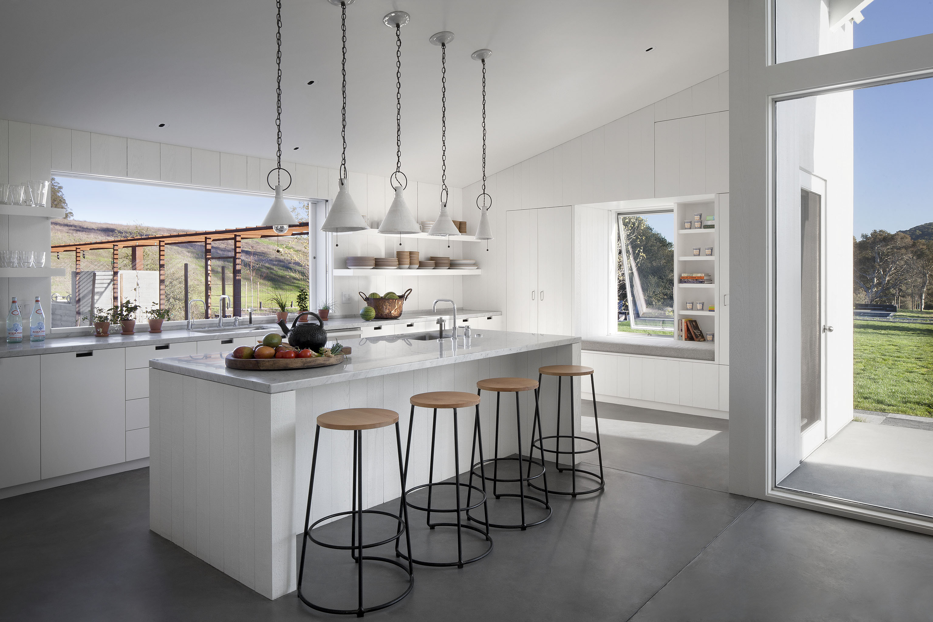 The open kitchen features a large marble topped island at center, beneath an array of pendant lights. Flanked by white built-in shelving, a massive sliding window over the sink allows for fresh air and wide vistas.