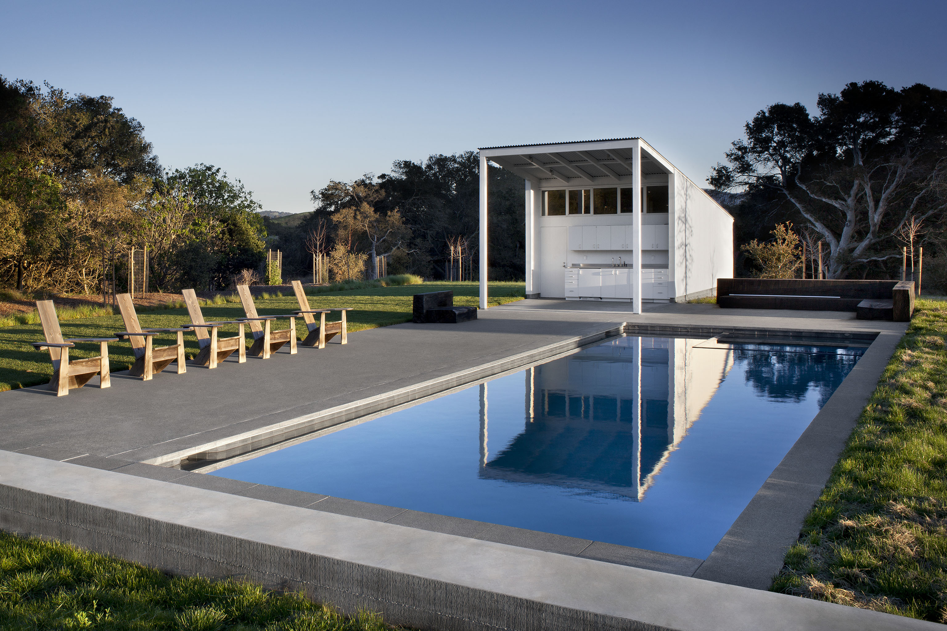 The extensive patio and pool area plays host to a large pool house, built in the same minimalist style as the barn home. An outdoor kitchen area complements the large patio, standing sheltered beneath an extended rooftop.