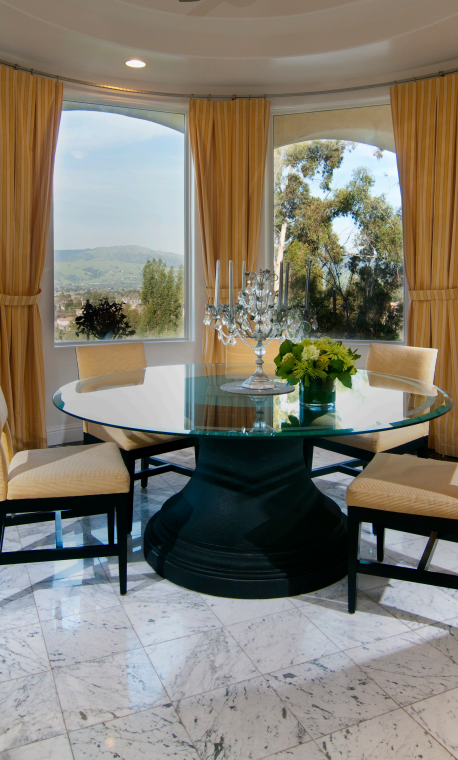 The dining room off of the kitchen has a delicate-looking glass-topped table with a candelabra centerpiece. The dark base of the table matches the dark wood of the dining chairs.