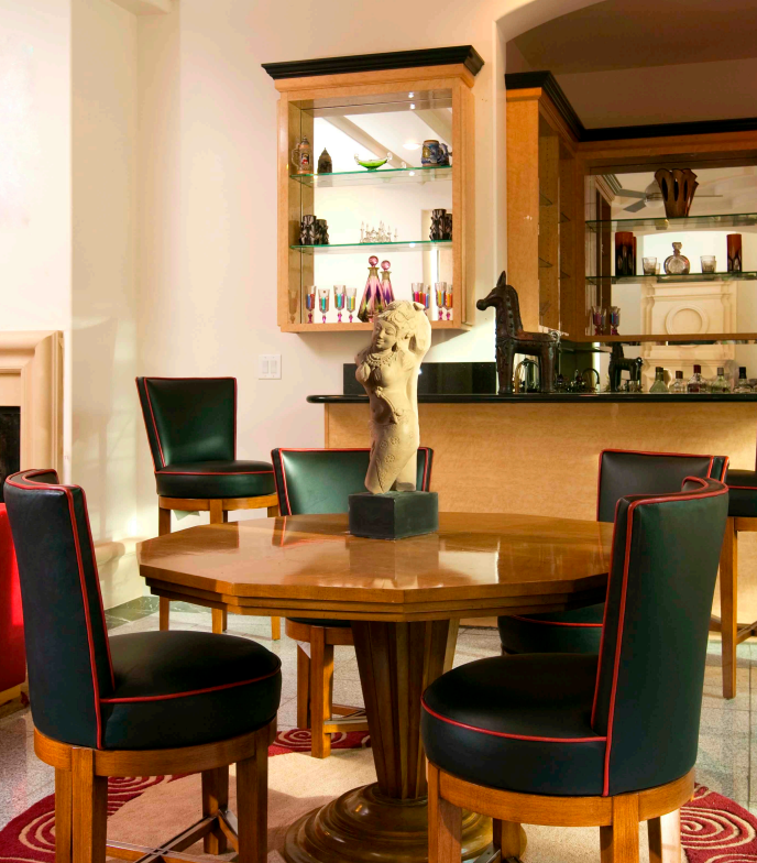 A more informal dining area next to the wet bar in the family room has a Hindu statuette as a centerpiece and dark seating with red piping. The red is repeated in the furniture of the family room and in the area rug beneath the table.