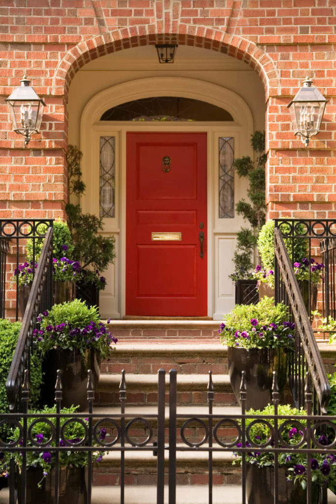 The front door features bronze lion door knocker, handle, and lock. The bright red door also has a golden metallic door mailbox slot at the center. The door is attached to white moldings and framing which has sidelights and a transom. Exterior lighting is fixed to either side of the brick facade around the porch. The steps to the front door are decorated with huge pots of blossoms and plants.