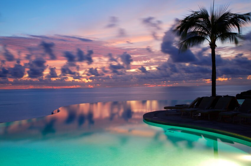 The pool lighting adds a green cast to the reflected sunset of this swimming pool. The curved line of the pool is barely noticeable and blends into the ocean beyond.