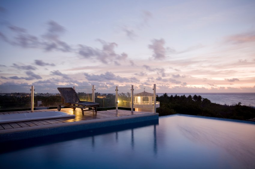 This infinity pool has a wooden patio extending to the left, with a glass-panel barrier and a hot tub. The view includes the top of a nearby lighthouse, the city just beyond the trees, and the water.