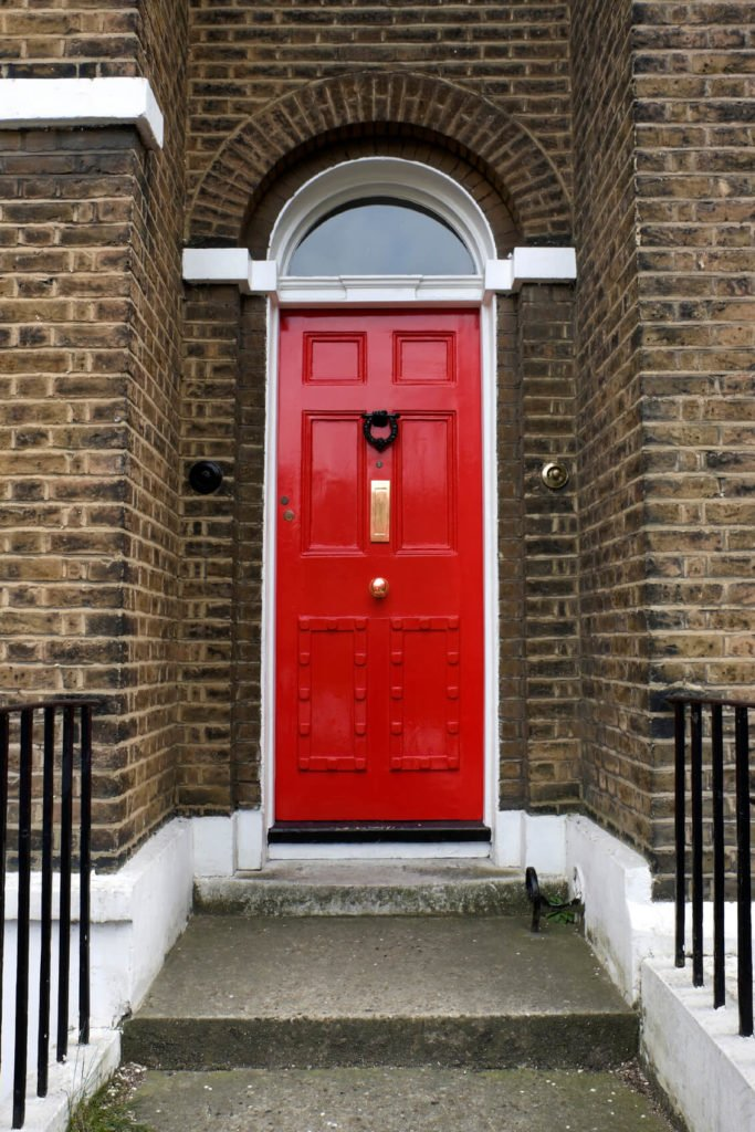 The arched door features a black metal door knocker, and golden mailbox slot and knob. The red-painted front door with raised upper panels also has a peephole just below the knocker and a lock on the left. The white-coated casting and framing strengthens the door with its arched transom of clear glass. Attached to the rough brown brick exterior, the steps leading up tot he door are concrete.