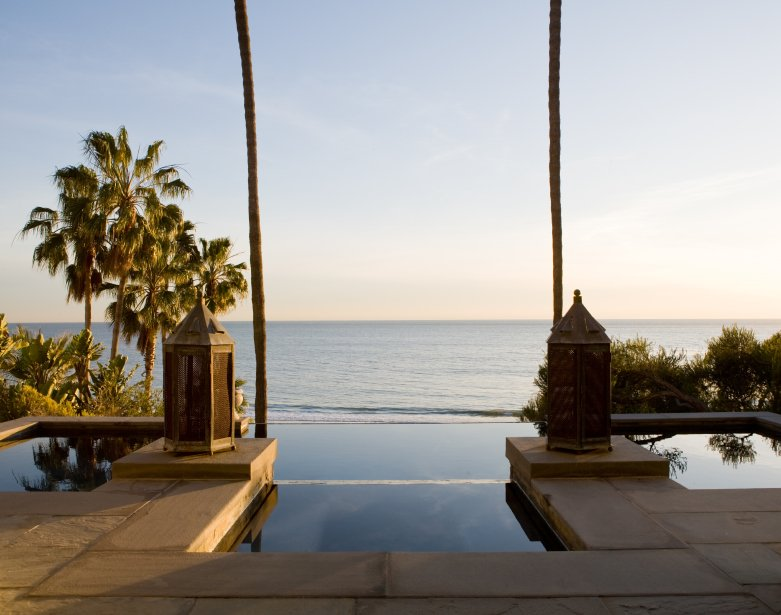 The limestone patio leads directly into the pool, which gets deeper once past the two posts lit by antique lanterns. Just beyond the edge of the pool is the beach, close enough to hear the waves roll in.
