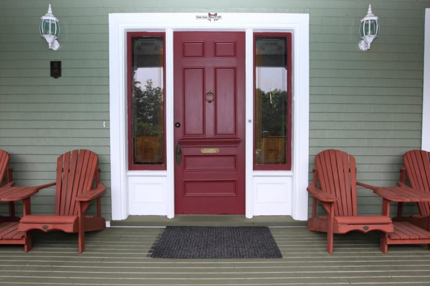 A bold red front door with sidelights and lounge chairs on either side.