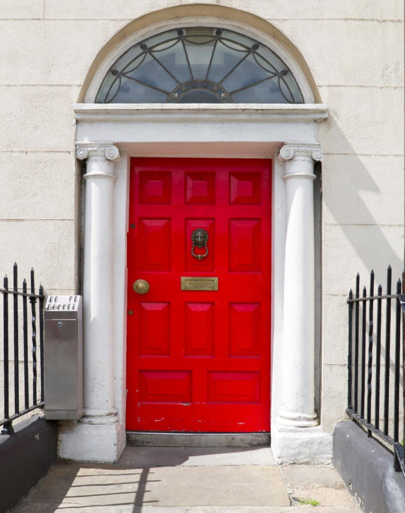 This door is very similar to the one above, with a lion's head knocker and white plaster pillars on either side. The narrow entryway has black iron railings on either side. The wear on the door and concrete shows the age of this home.