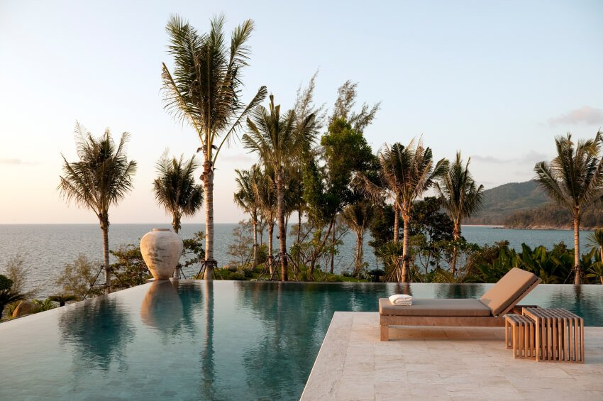 This infinity pool surrounds the limestone patio on three sides. the pool complex overlooks the water through the palm trees. On the corner, on the very edge of the pool is a decorative urn.
