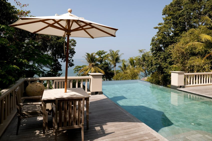 A more traditional example of a wooden deck with a wooden railing surrounding the infinity pool, which extends past the railing to overlook the trees that just obscure the ocean. A small, intimate seating area on the left is shaded by an umbrella.