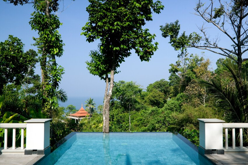 The design and location of this infinity pool is very similar to the previous pool, with slightly different trees. The tree at the end of the pool is near enough to reach out and touch. In the background is another building with a pagoda style roof.