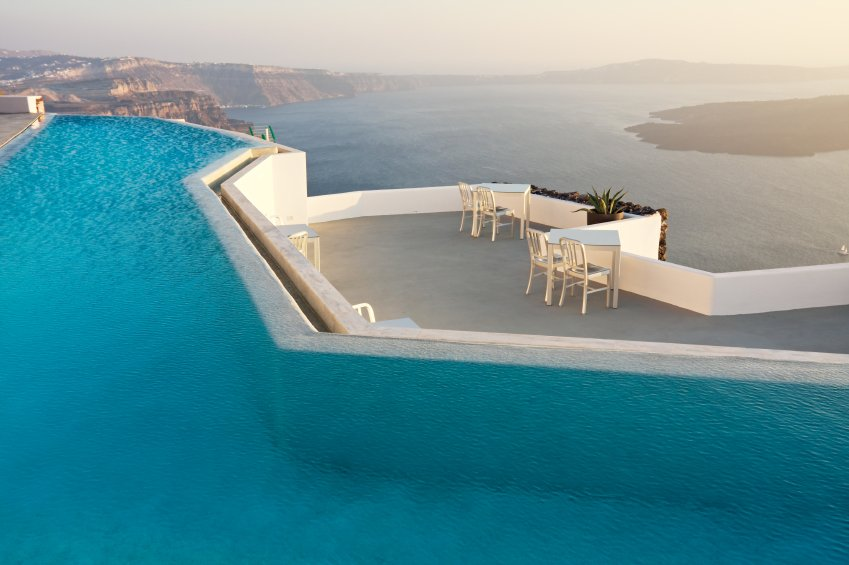This resort pool has a lower-level concrete patio with several small, intimate seating areas to look out over the water.