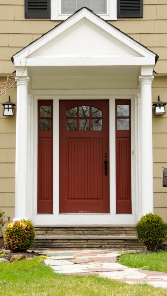 Instead of sidelights, which we see on most of these front doors, this entryway has panels on either side of the door that match the style of the door, and only very small glass windows at the very tops.