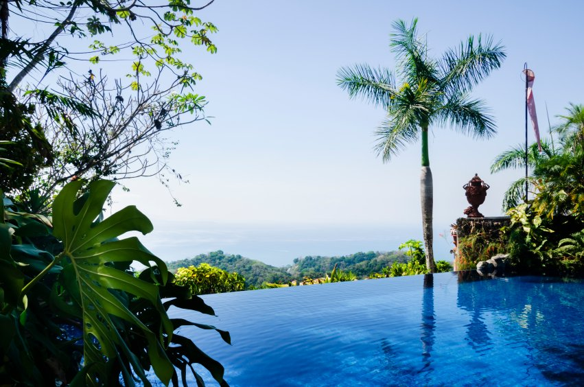 The deep blue pool is surrounded by leafy plants and a stone wall with an urn decoration. This example also looks over a tropical forest.