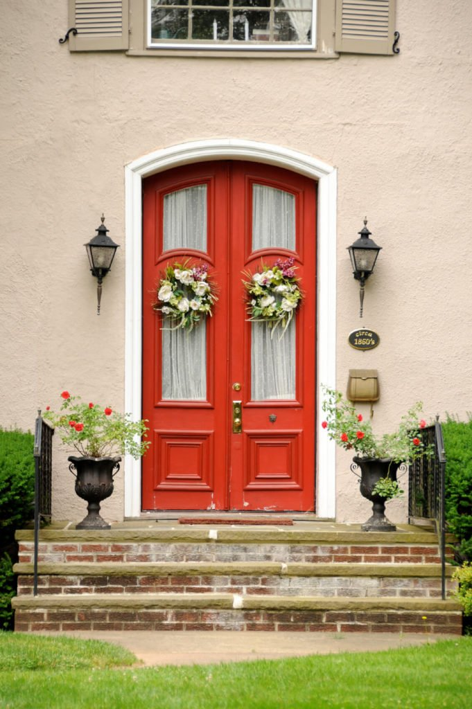 Aged brick steps lead up to this distressed, yet elegant front door. The front glass panels are obscured from the inside by polka-dotted curtains. The exterior of the door is brightened by elegant floral wreathes and matching urns used as planters. A plaque to the right of the door proudly proclaims that this is a historical home.
