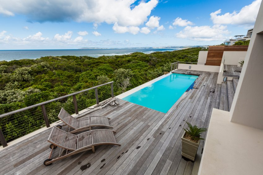 The light gray wood patio is also a balcony, with a beautiful, square infinity pool looking out over the landscape.