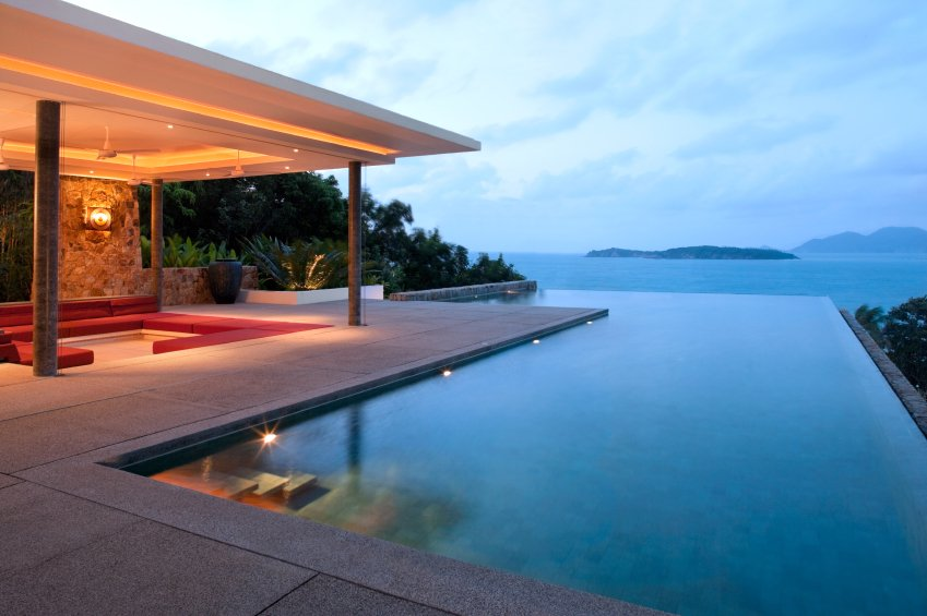 """The infinity pool has stairs leading into it from one corner of the patio. The covered seating area off to the left has a lowered red sectional that extends nearly all the way around the inset. The """"never-ending"""" effect of the pool is achieved by positioning the pool facing the open water."""