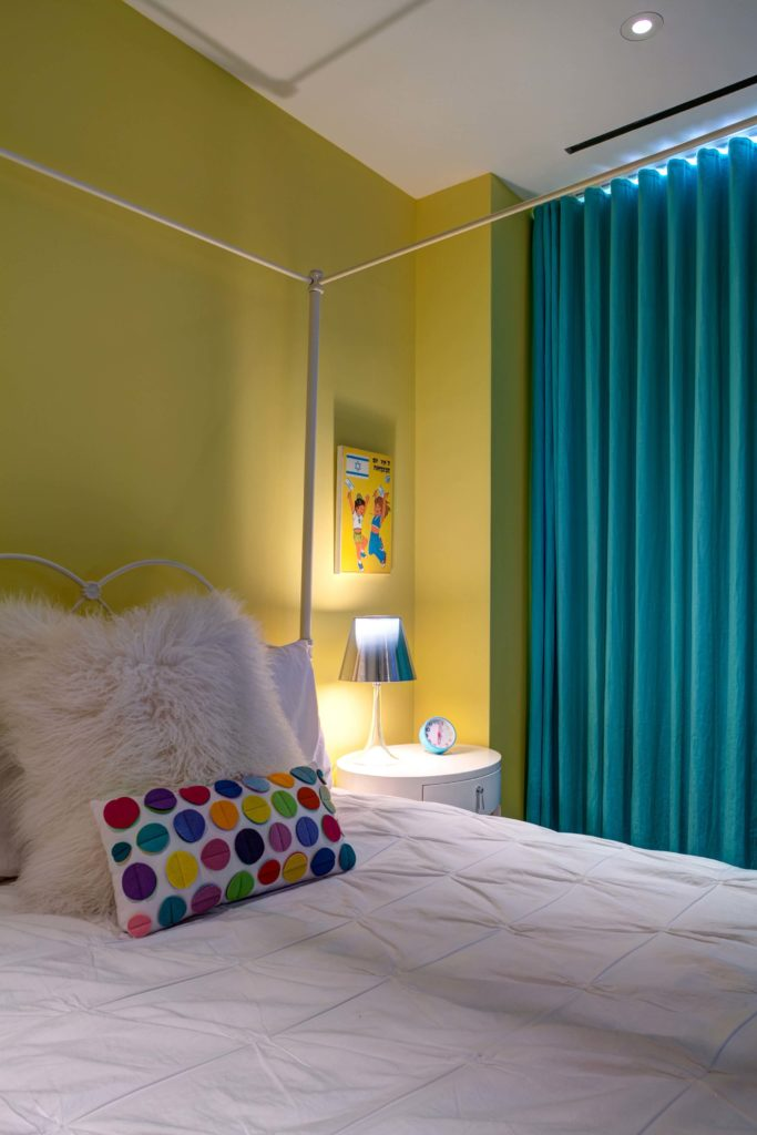 Here is one of the children's bedrooms, decked out in yellow walls and aqua curtains, with white bedding and bedside table. Polka dots make an appearance here, in rainbow colors.