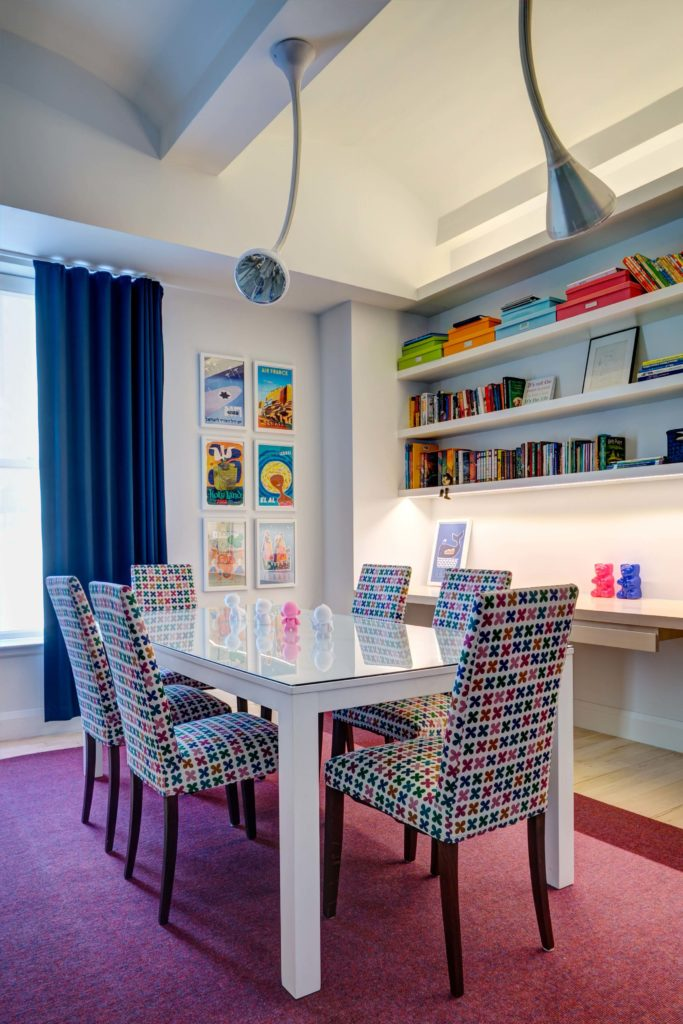 The large playroom holds a perfect mixture of lightness and color, with a white, glass-topped table surrounded by rainbow patterned accent chairs. Built-in shelving holds books, next to art pieces on the wall.