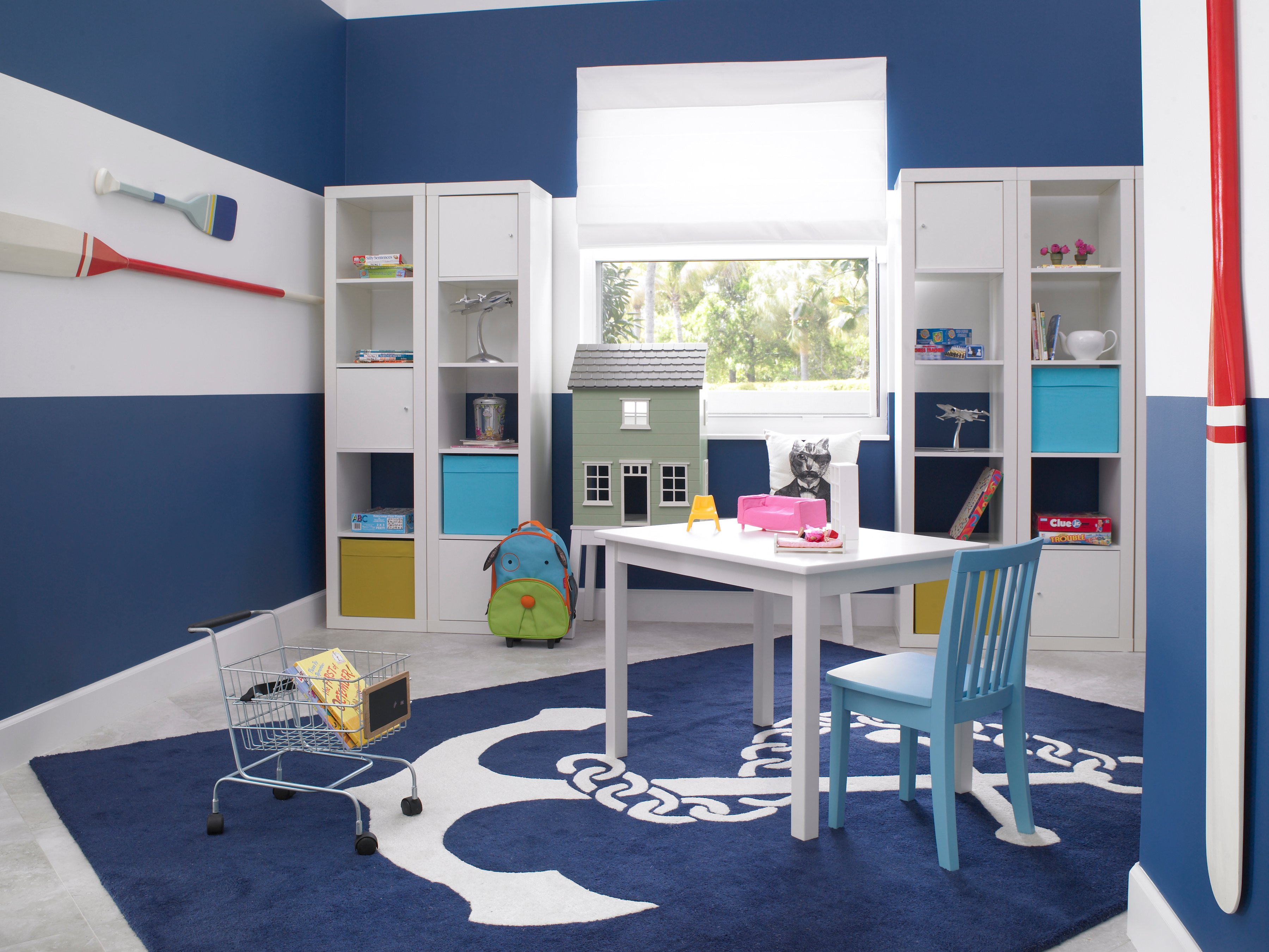 The play room is full of bright, fun colors, and the rug is emblazoned with an anchor. There is plenty of storage against the back wall for toys and games. The walls are in ultra-thick stripes, and decorated with paddles in blue, white, and red.