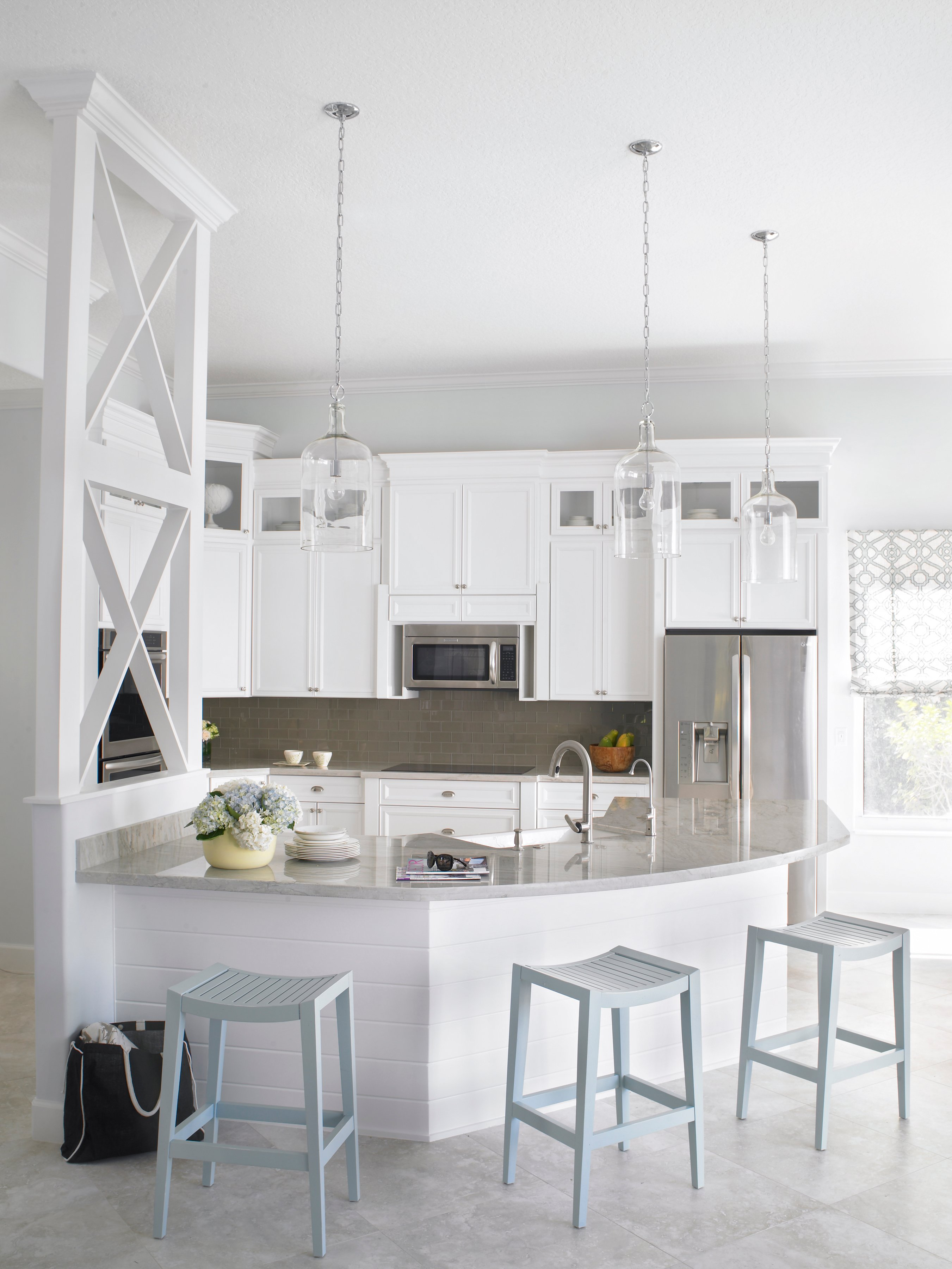This view of the kitchen shows the cooking area, with darker subway tiles in the backsplash. The kitchen island is shiplap painted white to match the rest of the kitchen. Separating one end of the bar and the work area is an elegant dividing wall with rustic charm. Glass pendant lights hang above the kitchen island.