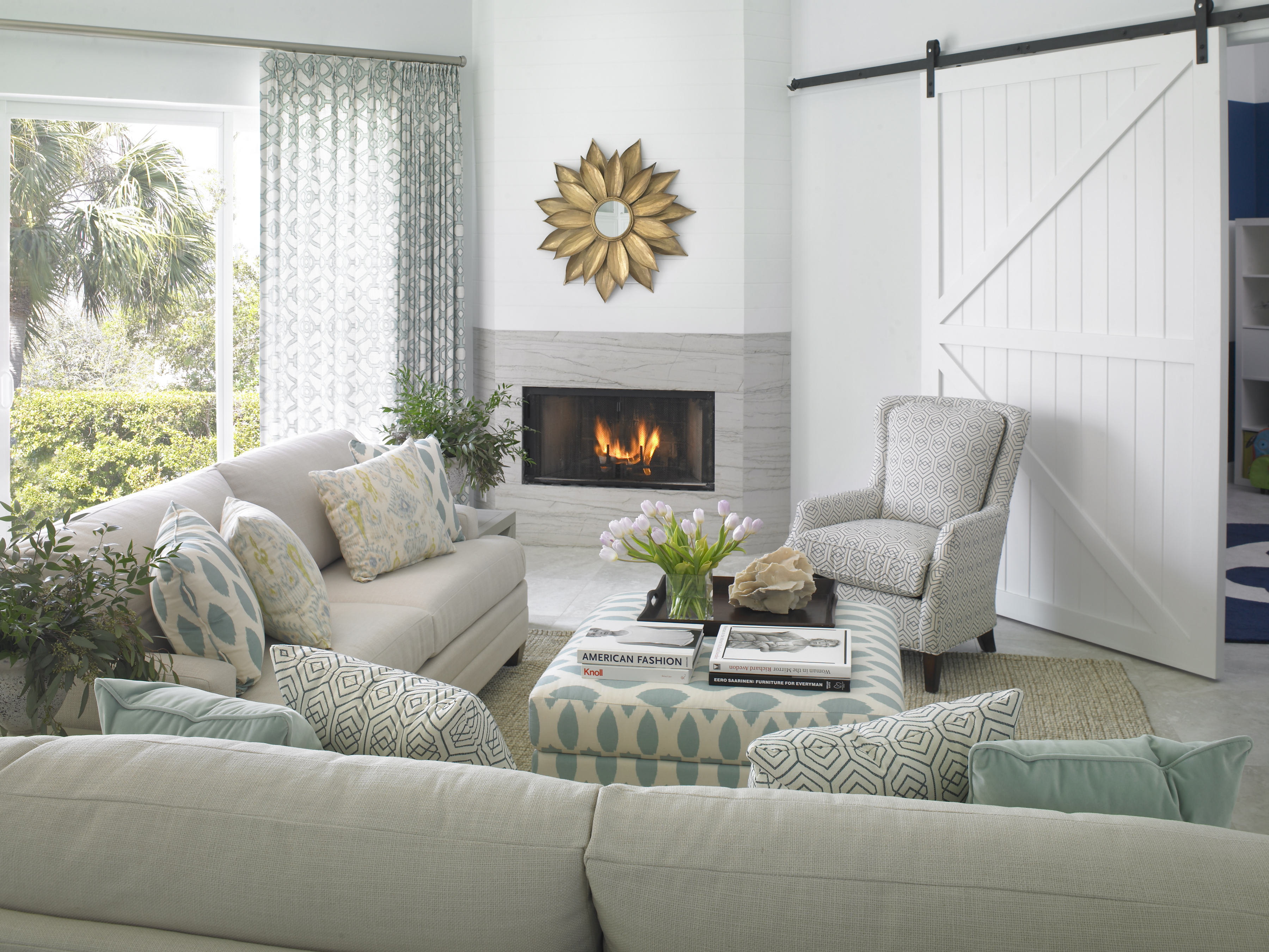 The enclosed fireplace has a gold floral mirror above it. A sliding barn door painted white leads into the playroom. The beautiful view includes the water, palm trees, and lots of greenery.