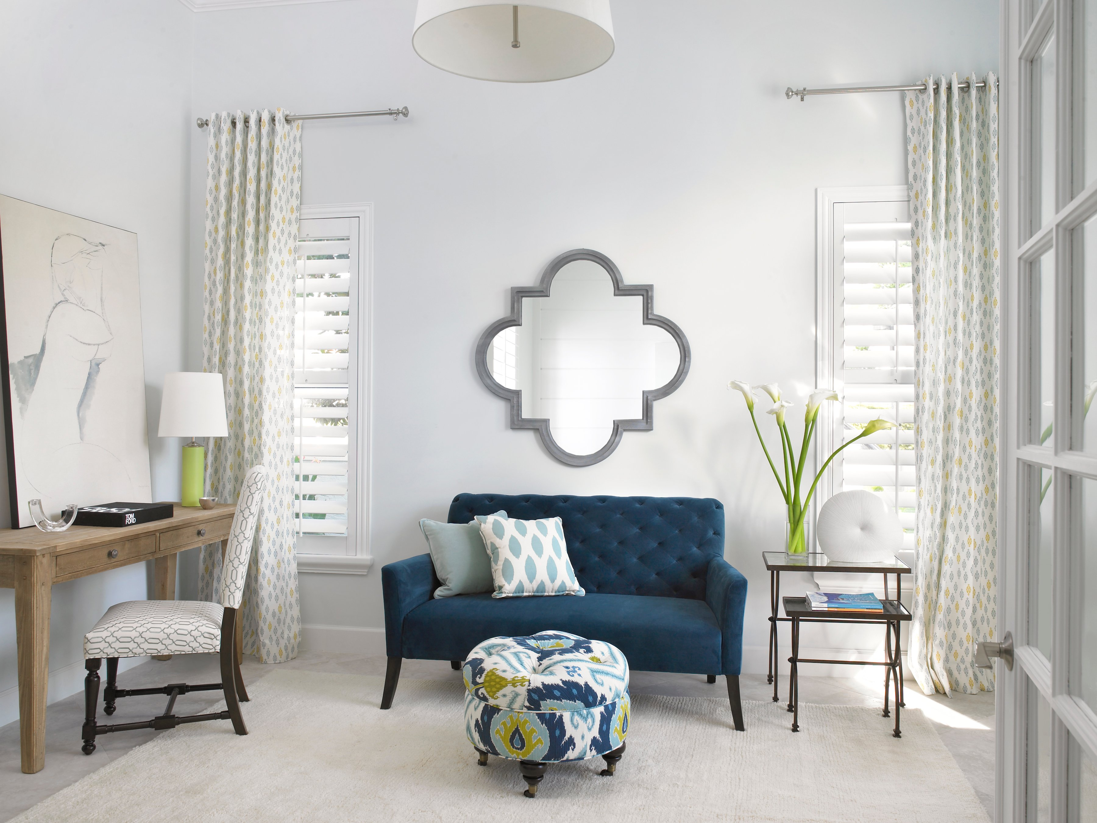 The home office is a light, airy space that promotes creative thinking. The blue velvet settee has a coordinating tufted ottoman that adds visual interest and warmth to the light color palette. A moroccan mirror hangs above the settee. The multiple patterns create a layering effect, rather than clashing. The simple desk is rustic, yet elegant, and a simple sketch adorns it, along with a small lamp and a glass paper weight. A glass vase with calla lilies is another perfect touch.