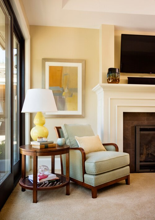 Next to the fireplace is a small reading nook with a cozy armchair and side table with a curvy yellow lamp.