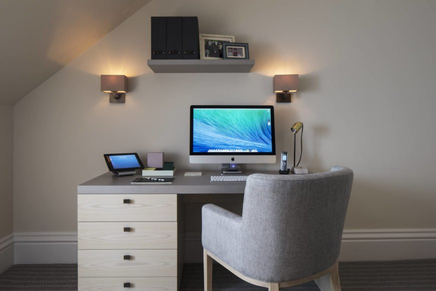 A contemporary light wood and grey desk stands with a matching upholstered armchair, below a pair of cubic sconces and minimalist wall shelf.