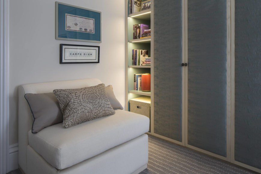 At the other end of the office, we have this armless deep cushioned chair and shelving with built-in lighting. Closet doors mirror the blue and white aesthetic of the living room.