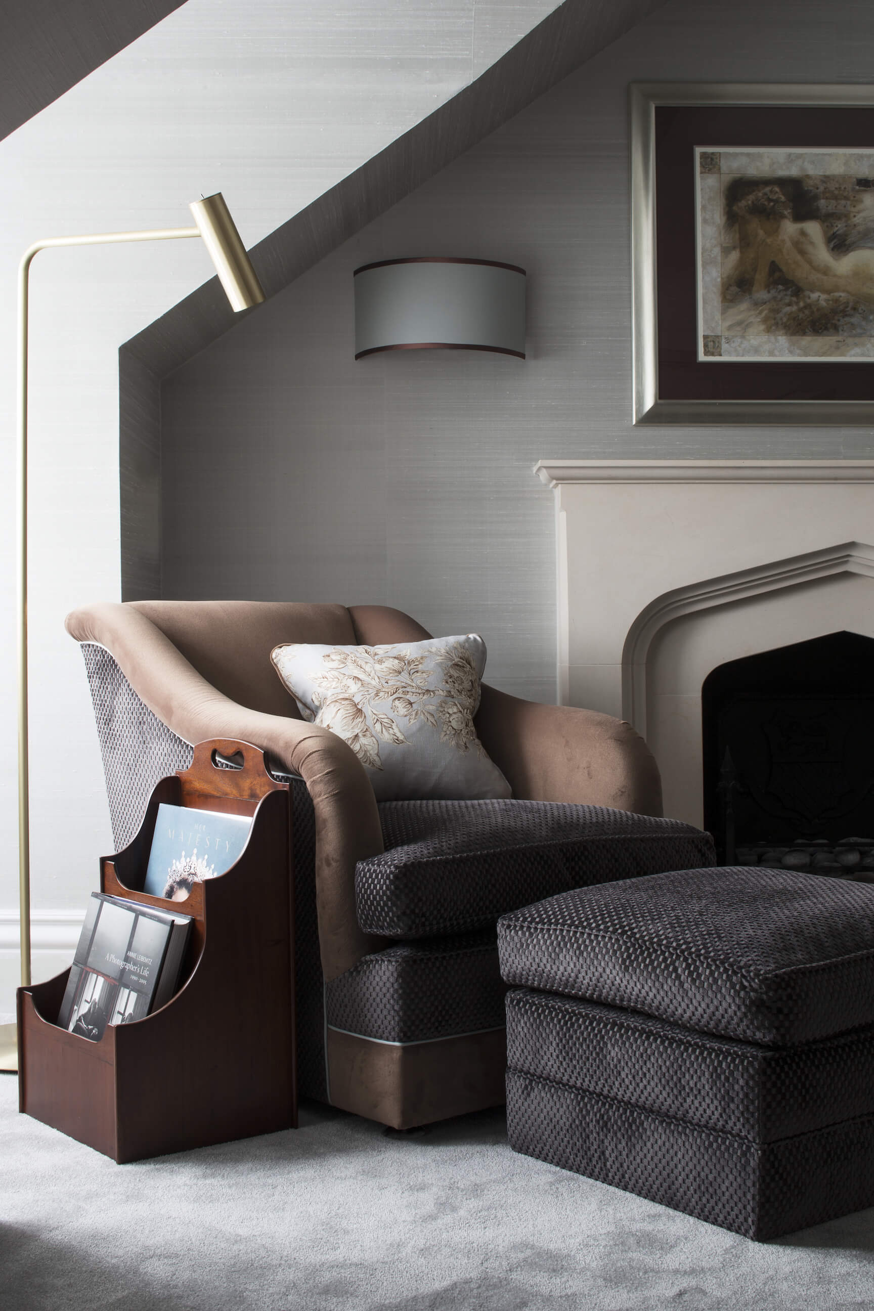 Beside the primary bedroom fireplace, we find this rich multi-textured club chair with matching ottoman, below a gold hued floor lamp and half-cylinder sconce.